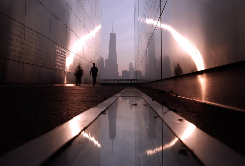 A man walks through the 9/11 Empty Sky memorial at sunrise across from New York's Lower Manhattan and One World Trade Center in Liberty State Park in Jersey City, New Jersey, September 11, 2013. Americans will commemorate the 12th anniversary of the September 11 attacks with solemn ceremonies and pledges to not forget the nearly 3,000 killed when hijacked jetliners crashed into the World Trade Center, the Pentagon, and a Pennsylvania field. REUTERS/Gary Hershorn (UNITED STATES - Tags: CITYSCAPE DISASTER ANNIVERSARY TPX IMAGES OF THE DAY) - RTX13HEO