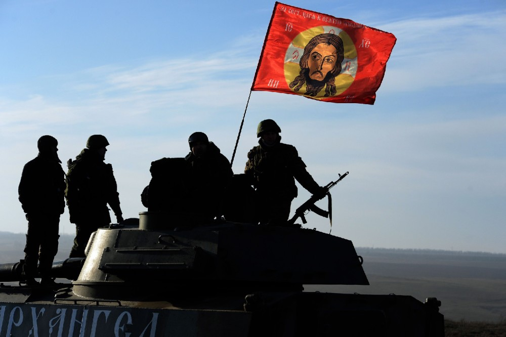 TOPSHOTS Pro-Russia militants sit next to a flag with the face of Jesus Christ as convoy of 2S1 Gvozdikas (122-mm self-propelled howitzers) takes a break as they move from the frontline near the eastern Ukrainian city of Starobeshevo in Donetsk region, on February 25, 2015.  France, Germany, Russia and Ukraine called on February 24 for a total ceasefire in eastern Ukraine as London announced it was sending troops to train government forces fighting pro-Russian separatists in eastern Ukraine. AFP PHOTO / VASILY MAXIMOVVASILY MAXIMOV/AFP/Getty Images