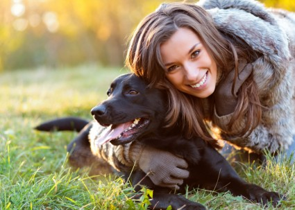 woman-with-dog-black-labrador-smiling-grass-sunshine